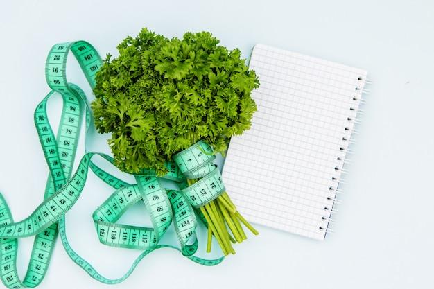 Verdes, fita de centímetro e um caderno vazio