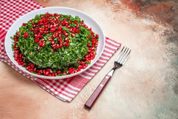 Verduras frescas com romãs descascadas em refeição leve de frutas verdes