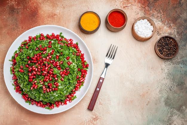 Verduras frescas com romãs descascadas em uma mesa de refeição leve com frutas verdes