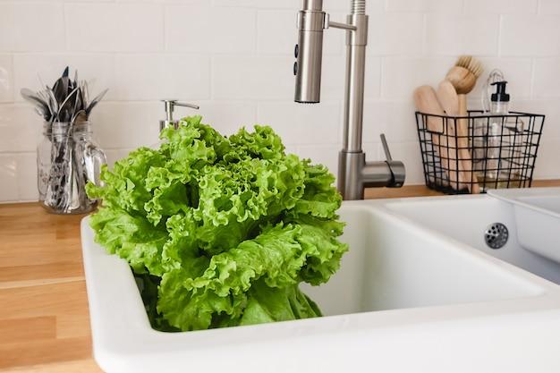 Verduras frescas e manjericão na pia da cozinha branca