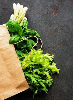 Verduras frescas em um saco de papel em uma mesa preta