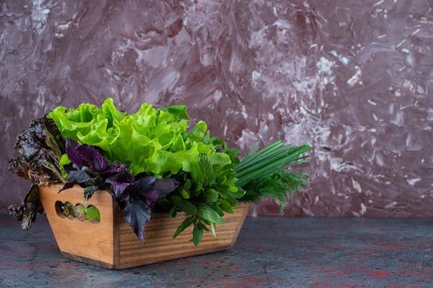 Verduras frescas em uma caixa, no fundo de mármore.