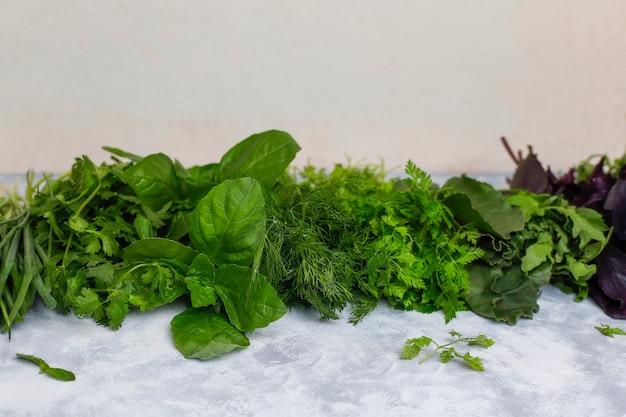 Verduras frescas manjericão, coentro, alface, manjericão roxo, coentro da montanha, endro, cebola verde em caixas plásticas em concreto cinza