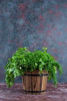 Verduras misturadas em um balde na superfície do mármore