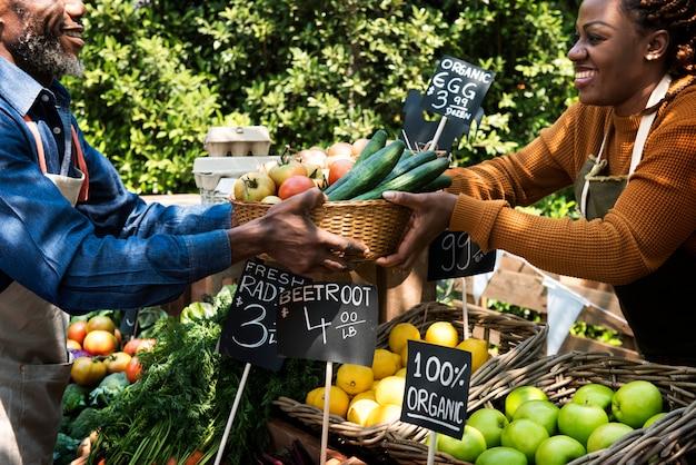 Verdureiro, preparando o produto agrícola fresco orgânico no mercado do fazendeiro