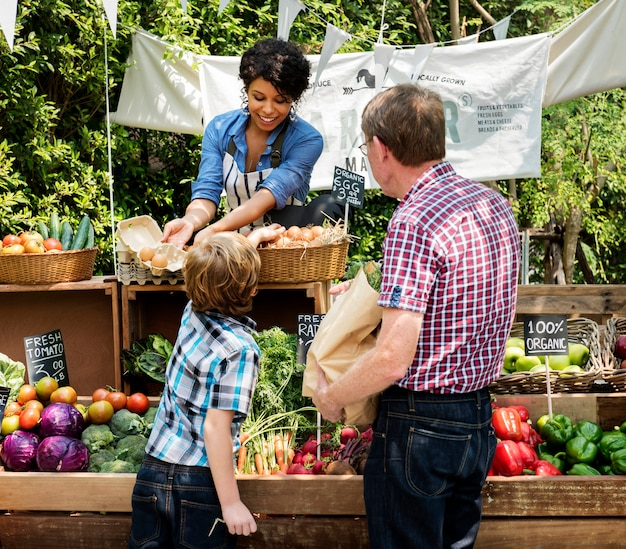 Verdureiro que vende o produto agricultural fresco orgânico no mercado do fazendeiro