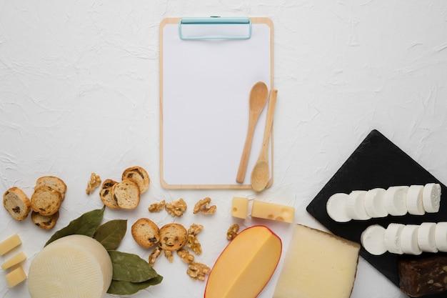 Veridade de queijo; fatia de pão; noz; folhas de louro com prancheta vazia