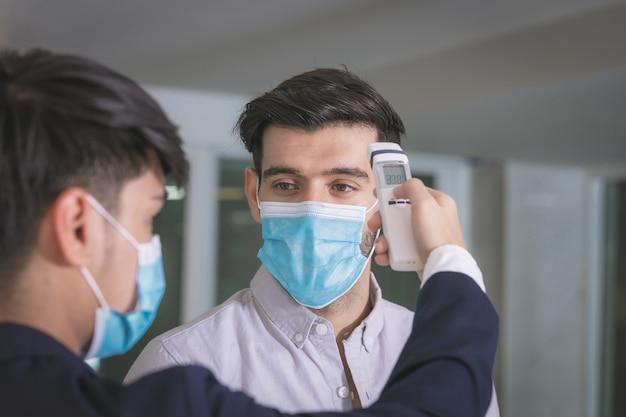Verificação da temperatura corporal, recepcionista e hóspede usando máscara facial na recepção enquanto conversam no hotel.