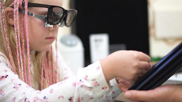 Verificação da visão. menina caucasiana que tem deficiências visuais