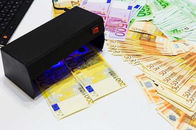 Verificação de autenticação de notas de euro em teste falso de dinheiro nas luzes do detector de moeda uv.