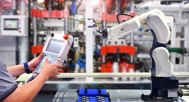 Verificação de engenheiros e automação de controle máquina de braço robótico para processos de embalagem de rolamentos automotivos na fábrica.