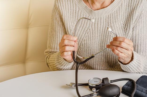 Verificação de pressão arterial em casa com dispositivo de estetoscópio. autocuidado e conceito médico.
