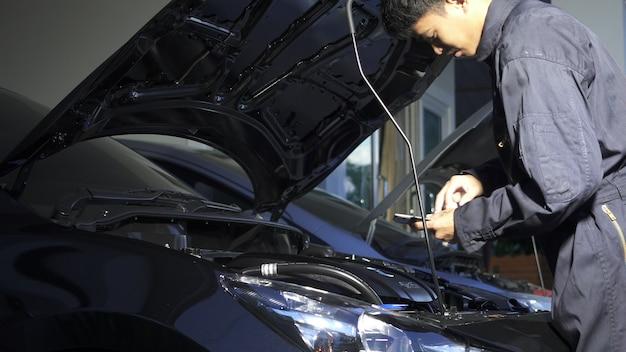 Verificação do homem mecânico, trabalhando no serviço de carro de oficina