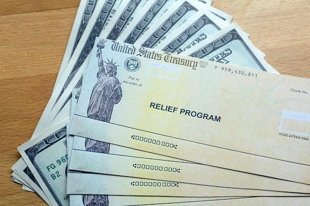 Verificações do programa de socorro dos eua e notas de dólar em fundo de madeira