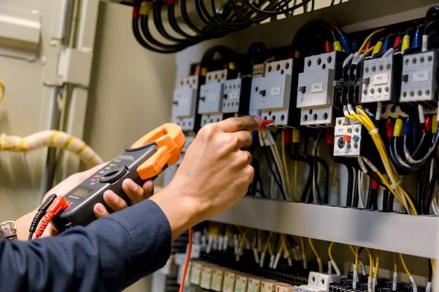 Verificador do trabalho do coordenador do eletricista que mede a tensão e a corrente da linha elétrica do poder no controle electical do armário.