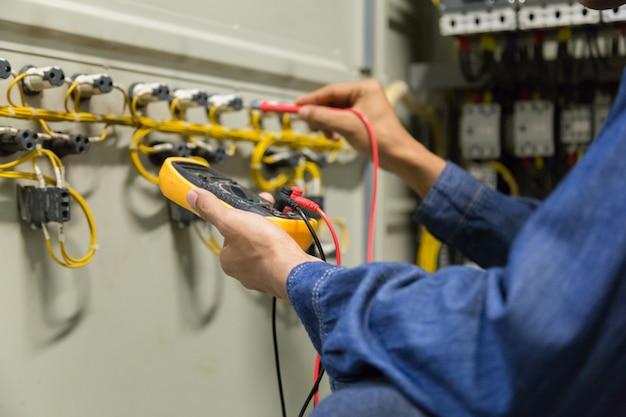 Verificador do trabalho do eletricista que mede a tensão da linha elétrica de poder.