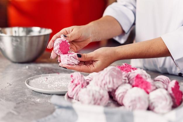 Verificando a qualidade do marshmallow caseiro. feche as mãos do chef com marshmallows feitos frescos.