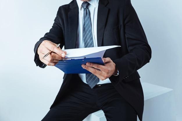 Verificando. aumentou a aparência de um trabalhador de escritório segurando uma prancheta e lendo suas notas escritas enquanto está sentado em um taco sobre o fundo.