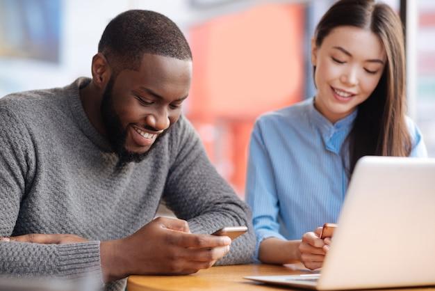 Verificando feed. par de jovens sorrindo, sentados à mesa com o laptop e envolvidos no uso de seus novos celulares.