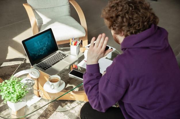 Verificando gráficos. homem que trabalha em casa durante a quarentena de coronavírus ou covid-19, conceito de escritório remoto. jovem empresário, gerente fazendo tarefas com smartphone, laptop, tablet tem conferência online.