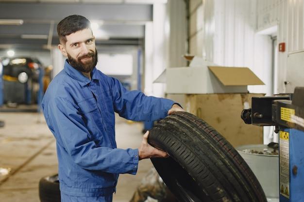 Verificando o carro para manutenção na garagem com ferramentas em ascensão