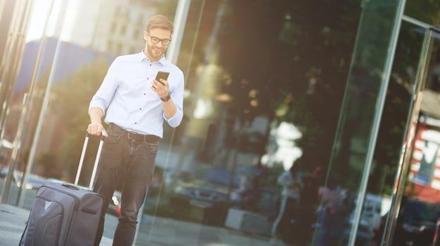 Verificando o e-mail do empresário bonito com a mala usando o smartphone e desviando o olhar em pé
