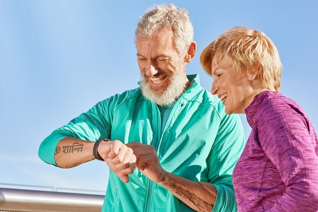 Verificando o retrato do tempo de um casal de família maduro ativo em roupas esportivas verificando os resultados durante o trabalho