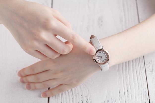 Verificando o tempo, relógio de pulso feminino na mão