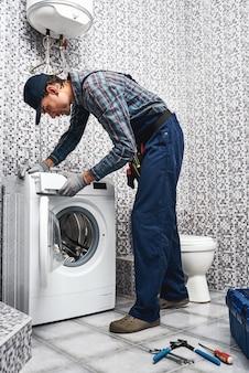 Verificando o trabalho da máquina de lavar, trabalhando homem encanador no banheiro
