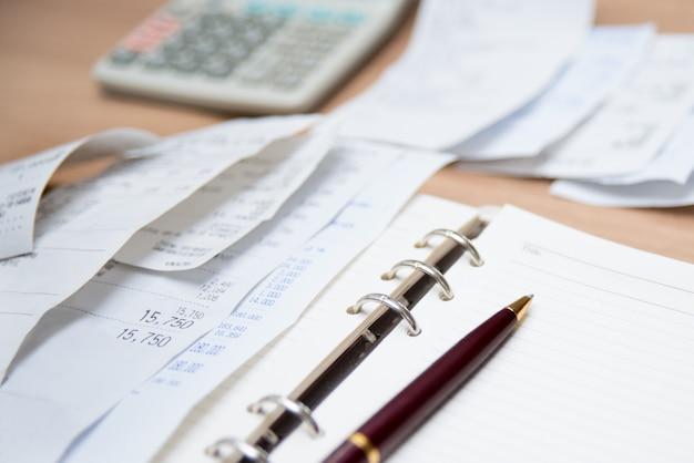 Verificando recibo. financie com recibos, calculadoras e notas. desfocado.