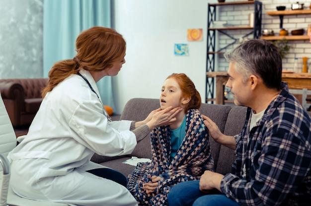 Verificando tudo. um bom médico profissional tocando o pescoço de seu paciente enquanto faz o exame médico