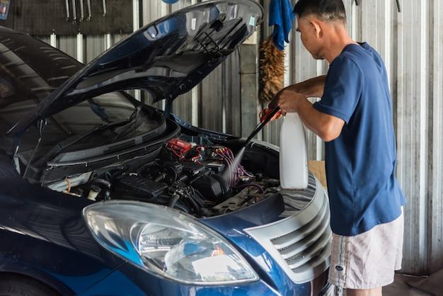 Verificando um motor de carro para reparação na garagem do carro