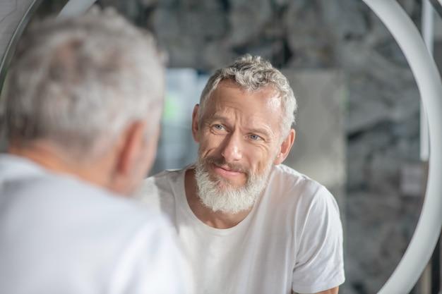 Verificando uma aparência. um homem de cabelos grisalhos olhando seu reflexo no espelho