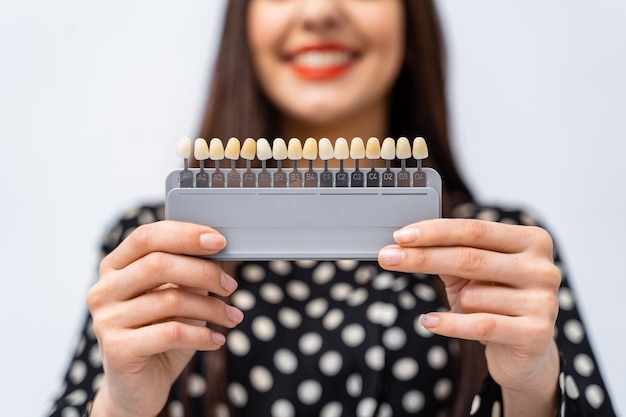 Verifique e selecione a cor dos dentes no consultório dentista. processo de escolha da cor dos dentes de uma linda jovem.
