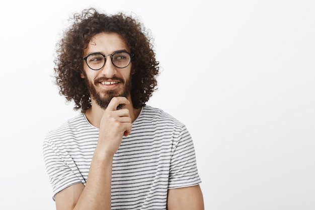 Verifique isso. rapaz atraente intrigado e sedutor em clima romântico brincalhão, segurando a mão na barba, parecendo bem e sorrindo com uma expressão de curiosidade satisfeita