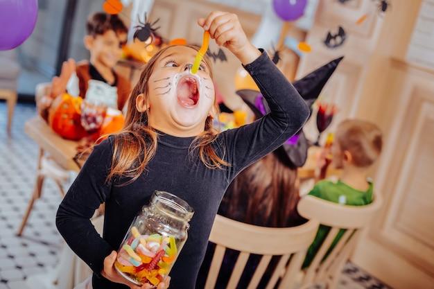 Verme da jarra. garota engraçada e fofa se sentindo animada e emocionalmente comendo minhoca de goma do pote durante o halloween
