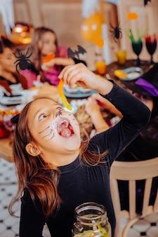 Verme viscoso. linda garota de cabelos escuros e fofa com rosto pintado usando roupa de halloween e comendo verme de goma