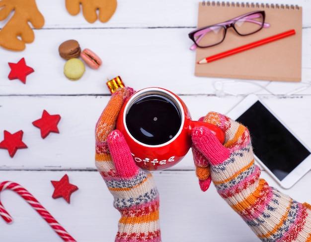 Vermelha xícara de café preto nas mãos femininas