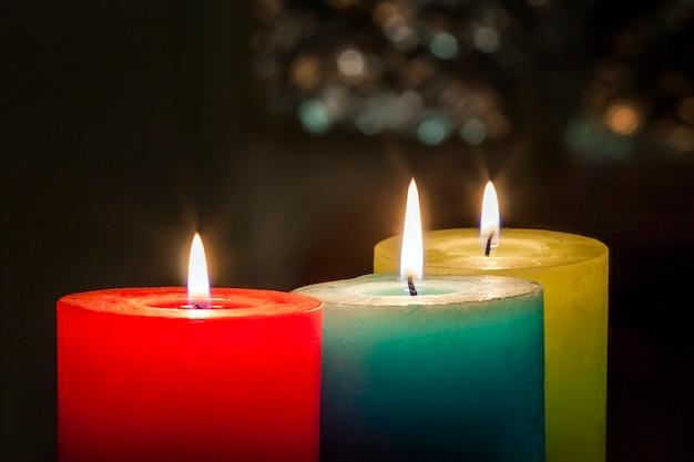 Vermelhas, amarelas e verdes velas coloridas com fundo desfocado bokeh. espaço de cópia de natal e ano novo.