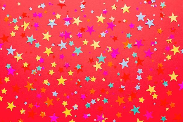 Vermelho festivo com confetes multicoloridos em formato de estrela