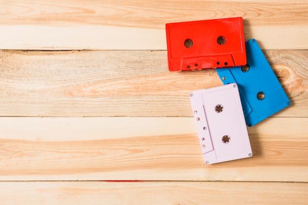 Vermelho; fita cassete áudio branco e azul na mesa de madeira