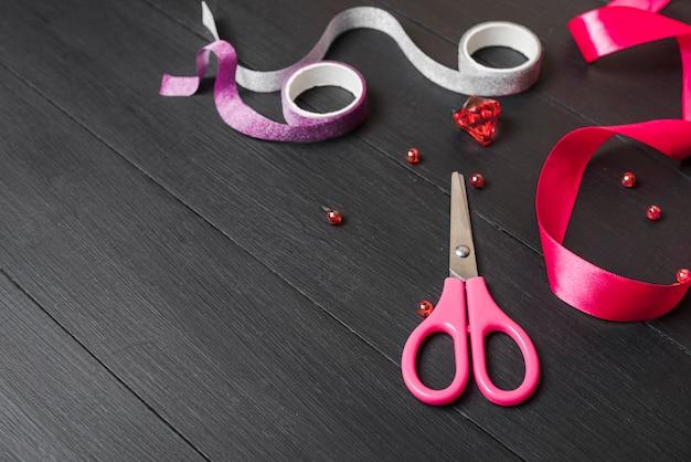 Vermelho; fitas roxas e prata com pérolas e tesoura na mesa de madeira preta