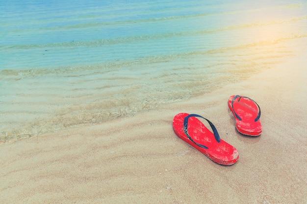 Vermelho flip-flops em uma praia de areia do oceano com forma de onda