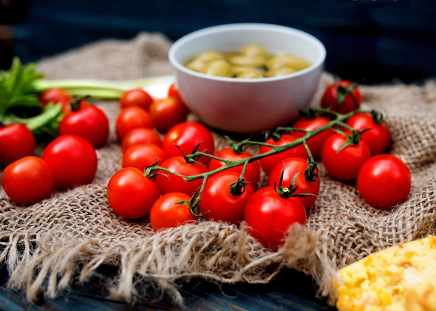 Vermelho fresco saboroso tomate cereja, cebolinha, azeitonas em madeira rústica escura