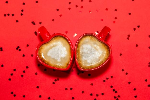 Vermelho par de canecas de café em forma de coração no fundo vermelho com corações de brilhos, vista superior