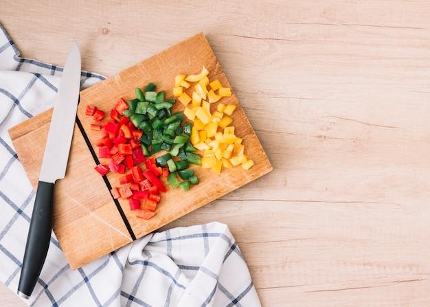 Vermelho picado orgânico fresco; pimentão amarelo e verde em cortar a placa com a faca sobre a mesa de madeira