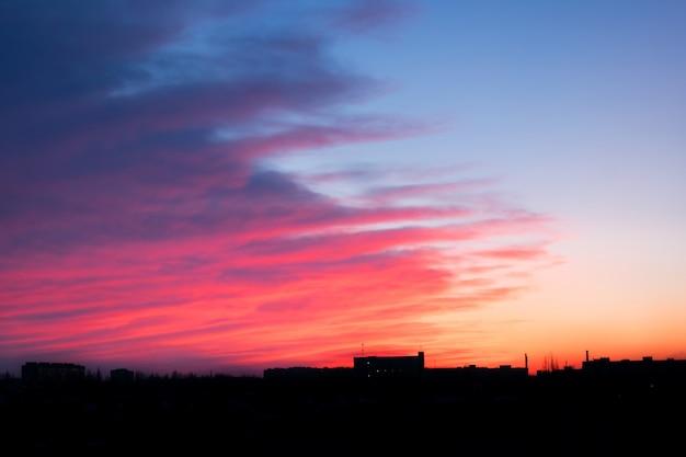 Vermelho rosa e azul brilhante pôr do sol sobre a cidade