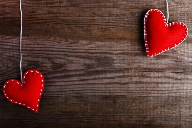 Vermelho sentiu corações em uma mesa de madeira. feito à mão em branco para cartões, espaço de cópia.