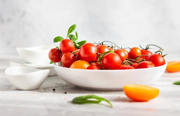 Vermelho tomate cereja e amarelo com espinafre no prato branco