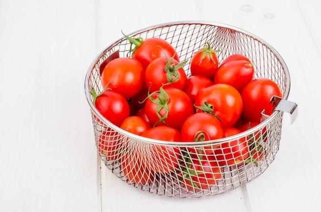 Vermelho tomate cereja maduro na mesa de madeira.